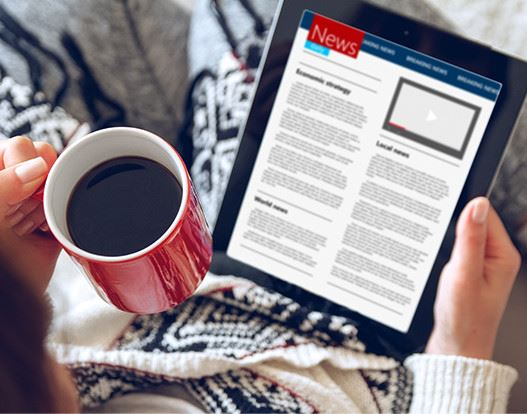 Women with a cup of coffee reading the news on her tablet