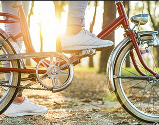 A person with tennis shoes putting their foot on a peddle of a red bike